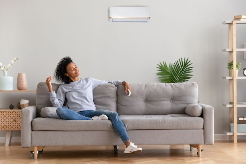 young relaxed woman sitting on couch breathing fresh air